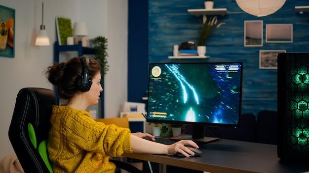 ヘッドセットを持ったプロのゲーマーが居間でオンラインビデオゲームをプレイし始めています。最新のストリーミングテクノロジーを使用して、強力なrgbコンピューターでゲームトーナメントをプレイするプロeスポーツチームプレーヤーストリーマー