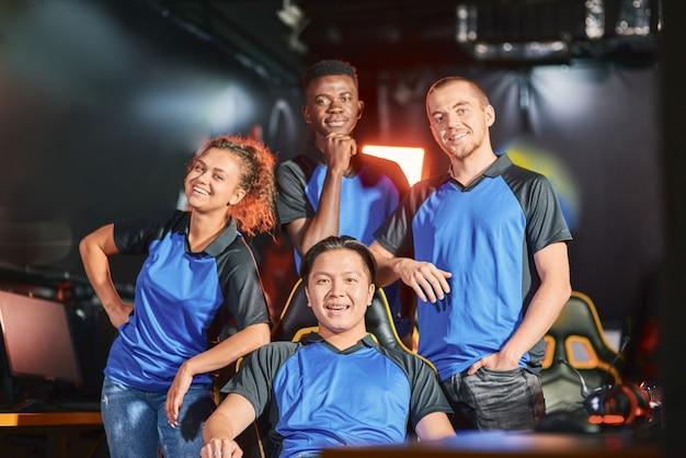 프로 게이머. e스포츠 토너먼트 후 카메라를 보며 웃고 있는 행복한 다인종 사이버스포츠 팀. 온라인 비디오 게임 대회