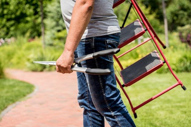 Профессиональный садовник идет рубить деревья садовыми ножницами и лестницей