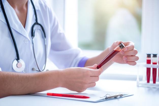 Профессиональный врач общей практики исследует образец крови из вены в больнице Premium Фотографии