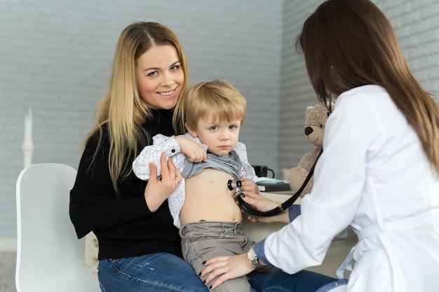 흰색 제복을 입은 전문 일반 소아과 의사는 청진기를 가진 어린이 환자의 폐와 심장 소리를 듣습니다.의사는 병원에서 상담한 후 아이 여성을 확인합니다