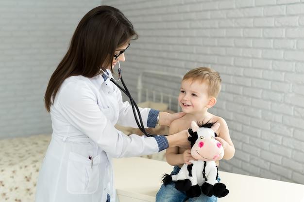 白い制服を着た専門の一般医療小児科医は、聴診器で子供の患者の肺と心音を聞きます。