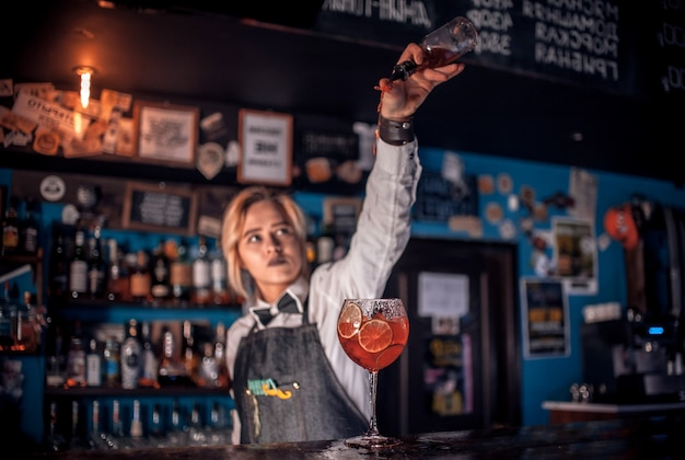 Professional girl bartender creates a cocktail in cocktail bars