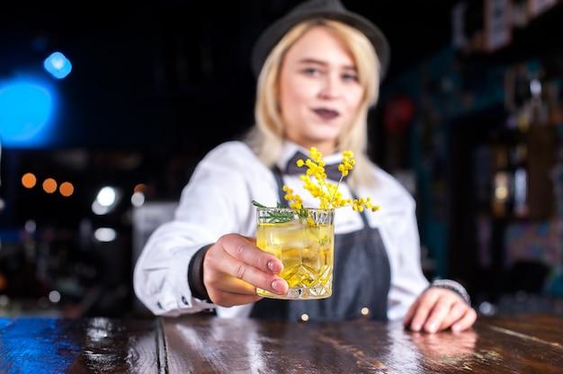 Профессиональная девушка-бармен готовит коктейль, стоя возле барной стойки в пабе