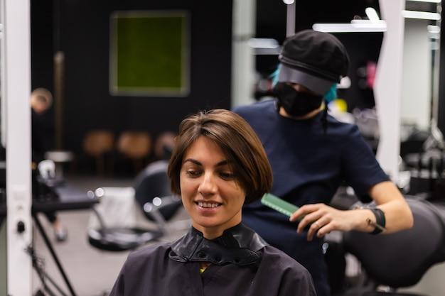 Un parrucchiere ragazza professionista fa un taglio di capelli del cliente. la ragazza è seduta in una maschera nel salone di bellezza