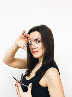 白い壁に彼女の手にはさみを持つプロの女の子の美容師。