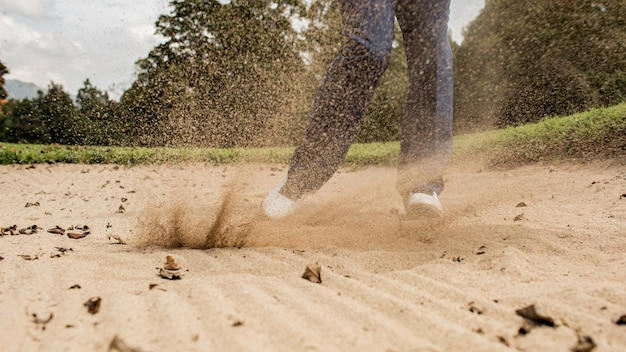 Professional golfer. hits the ball from the sand trap. bali. inodesia.