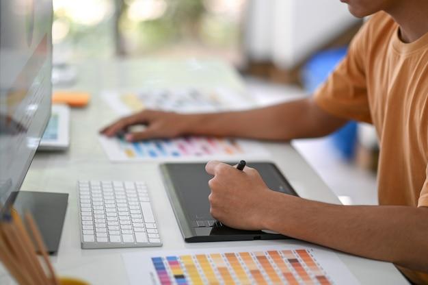 전문 그래픽 디자이너는 책상에 컬러 차트가있는 디지털 보드 작업을하고 있습니다.