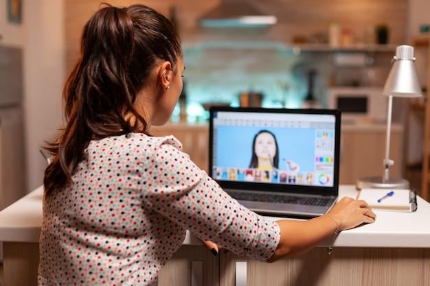ホームオフィスで夜間にクライアントの写真をレタッチするプロのグラフィックエディター。ソフトウェアとパフォーマンスのラップトップ、アーティスト、職業、ガラ場を使用してポートレートポストプロダクションを行う写真家