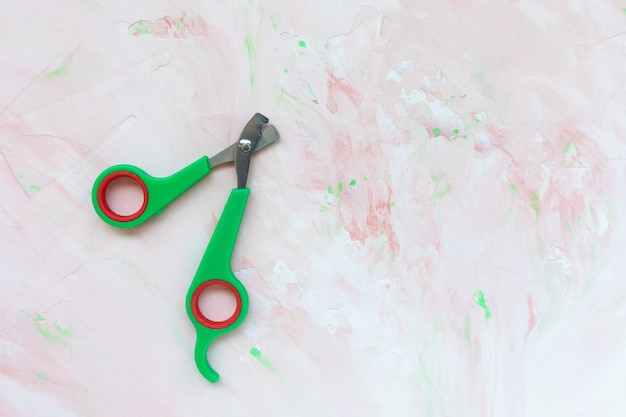 Professional green pet nail clippers for cats and dogs on pink wall, copy space. pet care, cat and dog trimmer claw concept