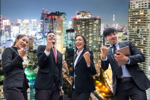 Professional group business person arm raised up be glad with successful on glowing light in the city background