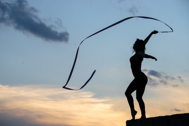 空にリボンを持つプロの体操選手の女性ダンサー。