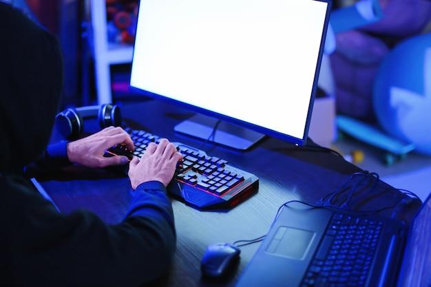 어두운 방에서 컴퓨터를 사용하는 전문 해커