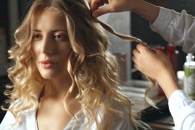 プロのヘアスタイリスト美容師が美容院で愛らしい金髪の女性にカールを作る/影でクローズアップショット