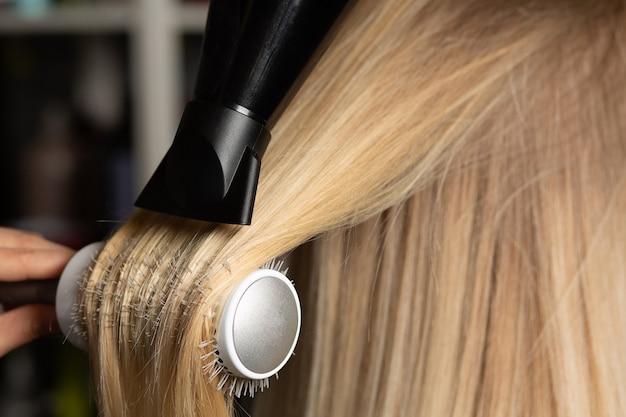 プロのヘアスタイリストがブラシコームとヘアドライヤーでクライアントの髪を乾かし、まっすぐにします