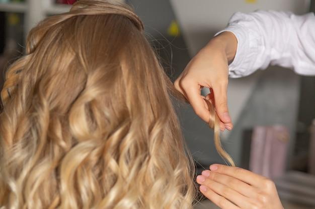 ビューティーサロンでヘアスタイリング中にクライアントのカールを保持しているプロのヘアスタイリスト。クローズアップショット