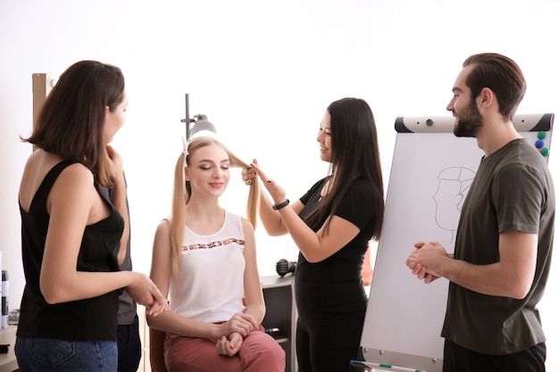 サロンでクライアントと一緒に働くプロの美容師と研修生。見習いの概念