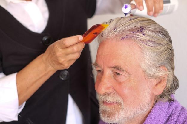 Профессиональный парикмахер нанесет особый фиолетовый цвет на белые волосы пожилого мужчины.