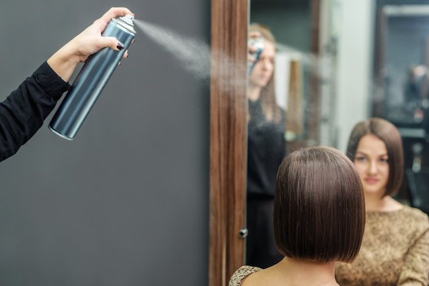 Professional hairdresser applying hair spray on short hairdo in beauty salon
