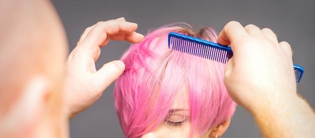 Профессиональный парикмахер проверяет прическу с расческой молодой красивой кавказской женщины