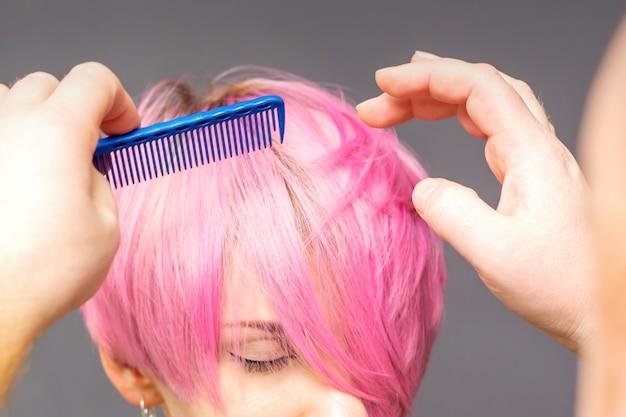 Профессиональный парикмахер проверяет прическу с расческой молодой красивой кавказской женщины.