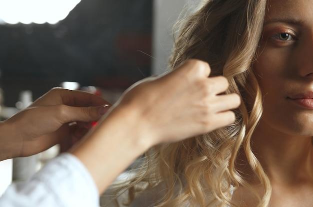美容院でクライアントの髪をカーリングするプロの美容師。クローズアップショット