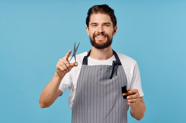 Professional hairdresser in gray aprons fashionable hairstyle bushy beard scissors comb man