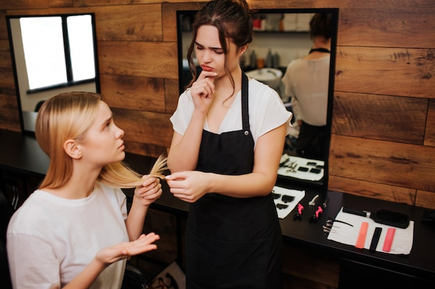 전문 미용사는 여성 고객의 나쁜 말린 끝을 손에 들고 효과적인 수리에 대해 생각합니다. 미용실에서 헤어 스타일을하기 전에 관리