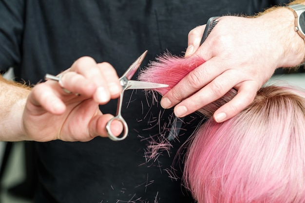 Professional hairdresser is holding in hand between fingers lock of red hair and cuts hair tips