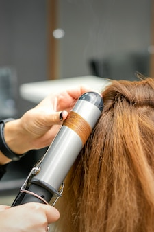 Professional hairdresser makes curls with a curling iron for a young woman with long red hair in a beauty salon
