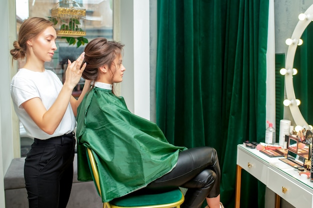 Professional hairdresser makes hairstyle for woman in beauty salon.