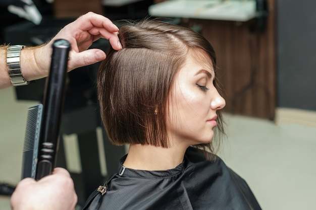 Professional hairdresser makes hairstyle