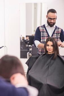 ブルネットの少女の髪を作るプロの美容師。