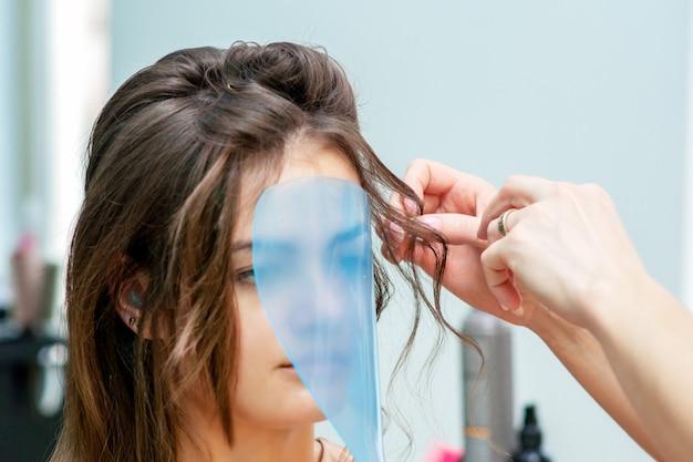 Профессиональный парикмахер делает прическу для женщины во время защитной маски на лице в салоне красоты.