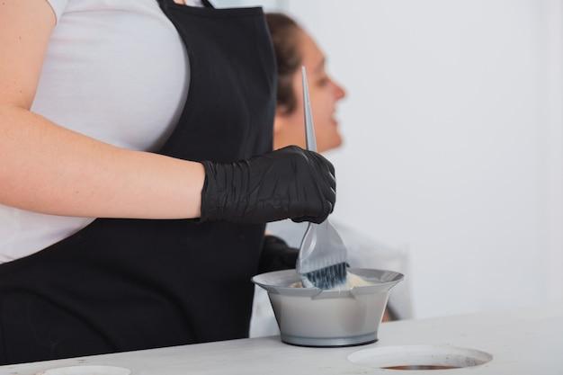 ヘアダイ クリームを準備するプロの美容師の手。