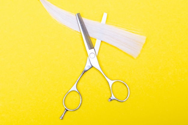 Professional hairdresser's scissors and strand of blonde hair on yellow background