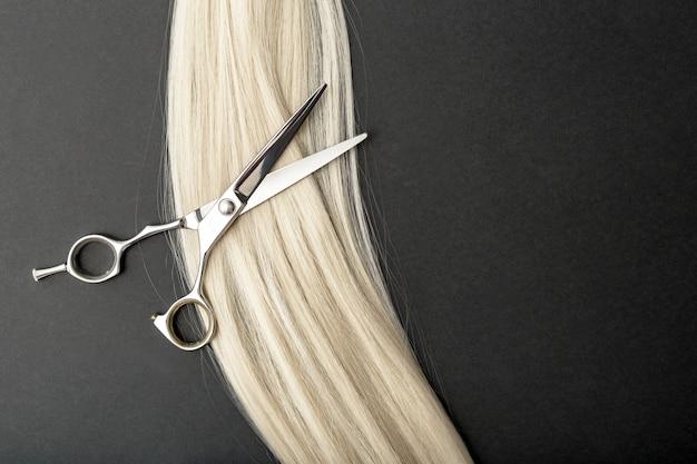 黒いテーブルの上のブロンドの髪の長いストランドを持つプロの美容師はさみ。フラット横たわっていた構成。