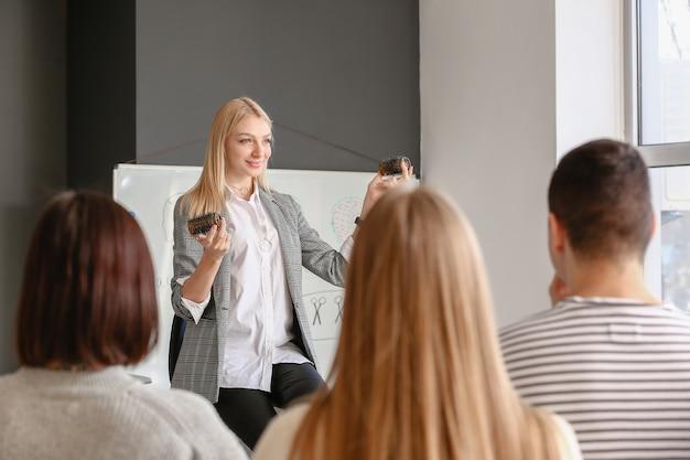 Профессиональный парикмахер обучает молодых людей в офисе