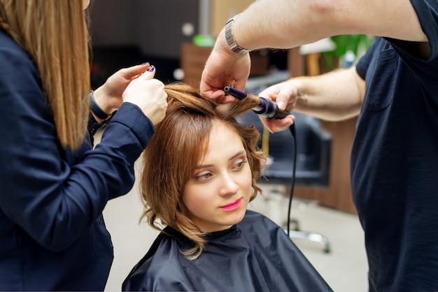 プロの美容師が美容院でカーリングアイロンで女性の長い光の茶色の髪のカールをツイストします。理髪の手順