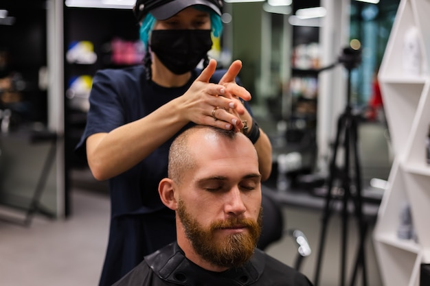 Parrucchiere professionista che indossa maschera protettiva, taglio di capelli per uomo brutale barbuto europeo nel salone di bellezza