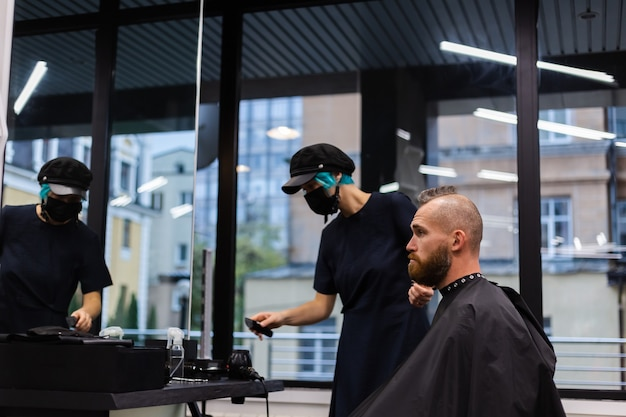 보호 얼굴 마스크를 착용하는 전문 미용사, 뷰티 살롱에서 유럽 수염 난 잔인한 남자를위한 이발 만들기