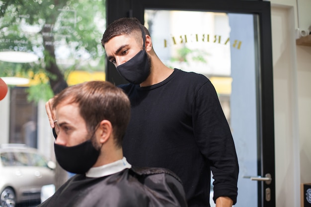 Professional hairdresser wearing protective mask cutting the hair to a client during coronavirus