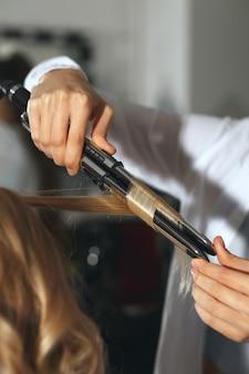 Профессиональный парикмахер, работающий со светловолосой женщиной в парикмахерской. создание красивых локонов плойкой