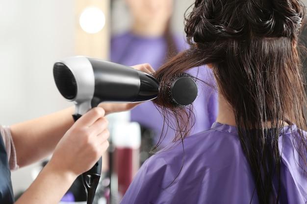 Профессиональный парикмахер, работающий с клиентом в салоне