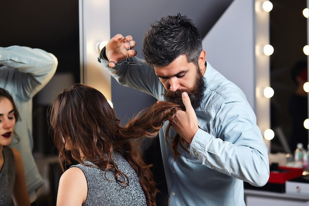 Professional hairdresser working with fashion brunette model with long curly hair at luxury salon