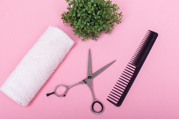 ピンクの背景にプロの美容師はさみとブラシ