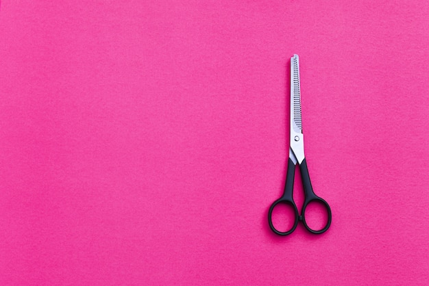 Professional hairdressing scissors on pink background