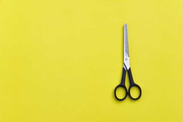 Professional hairdressing scissors on yellow background