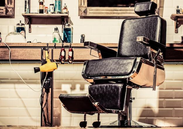 이발소 내부의 전문 미용사. 이발소 인테리어. 이발소 의자. 이발소 안락의자, 현대적인 미용사 및 미용실, 남성용 이발소. 세련된 빈티지 이발소 의자.