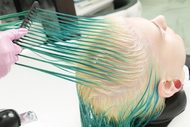 Professional hairstylist in protective glove holds of hair in hand and brushes long green and bleached hair of client, while washing head in shower in special sink of beauty salon.